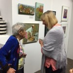 Bea discussing her painting (The Grape Seller, to her left) with a patron.