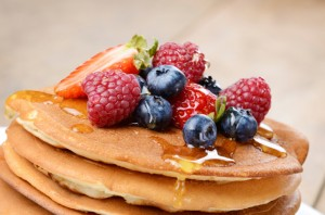 Pancakes with berries and honey closeup