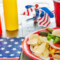 A cheeseburger at a patriotic themed BBQ is loaded with toppings that include ketchup, mustard, onion, tomato and lettuce.  It is being served with potato chips, pickles and ice tea.