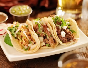 close up photo of authentic mexican barbacoa, carnitas and chicken tacos shot with selective focus.