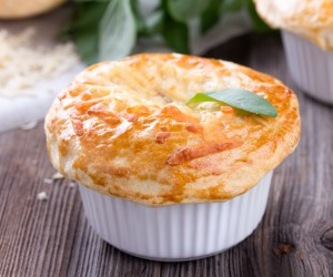 Chicken pot pie with cheese and basil on rustic wooden table