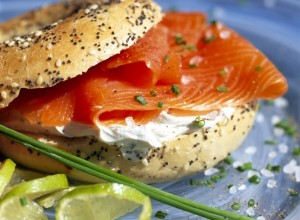Smoked Salmon and Cream Cheese In a Seeded Bagel served on a blue plate with a lime garnish and chives, for breakfast lunch or evening meal, brunch, healthy eating, healthy food, diet, dieting, wellbeing, healthy lifestyle, isolated against a white background, clipping path or cut out,