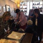 Our residents perusing Cal's portfolios and framed paintings.